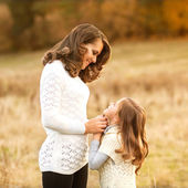 Mother and daughter walking in autumn in a field — Stock Photo