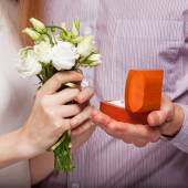 Wedding couple holding ring box and a bouquet of flowers — Stock Photo