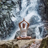 A young man engaged to a waterfall in the mountains of yoga — Zdjęcie stockowe