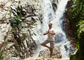 Sporty young man practicing yoga near a waterfall in the mountai — Stock Photo