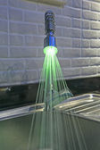 Ornate iluminated tap in kitchen — Stock Photo