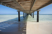 Wooden jetty on tropical beach — Stock Photo