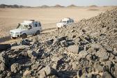 Vehicles driving through rocky desert — Stock Photo