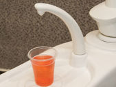 Cup of mouthwash drink in dentists surgery — Stock Photo