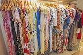 Womens summer clothes hanging on rail — Stock Photo