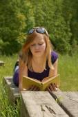 Young girl reading a book in the park — Stock Photo