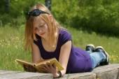 молодая девушка, читая книгу в парке — Стоковое фото