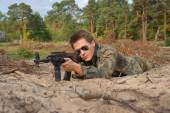 Teenager, boy lying in his battle dress, sunglasses and a rifle, Air Soft Gun — Stock Photo