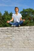 Teenager, boy sitting on a wall and meditates — Stock Photo