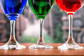 Glasses with blue red and green liquid cocktails — Stock Photo
