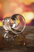 Glass of rum whiskey over defocused lights background — Photo
