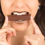 Beautiful young brunette girl eating chocolate — Stock Photo #54931461