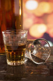 Glass of rum whiskey over defocused lights background — Stock Photo