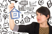 Young beautiful woman drawing a house with marker — Stockfoto