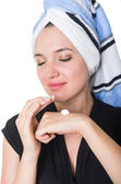 Beautiful young woman applying cleaning cream moisturizer to her face — Stock Photo
