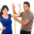 Handsome man holding measuring tape around thin young girl — Stock Photo #58325593