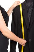 Tailors hand measuring a black suit — Stock Photo