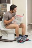 Young relaxed man sitting on the toilet reading newspaper — ストック写真