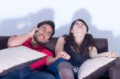 Bored girlfriend watching tv while boyfriend chats on the phone — Stock Photo