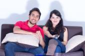 Young attractive couple watching movie at home — Stock Photo