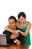 Young attractive happy couple in front of computer buying online with credit card — Stock Photo