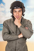 Young handsome pilot wearing uniform and helmet over beach background — Stock fotografie