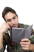 Distraught military soldier veteran holding a bottle and looking at photos ptsd — Stock Photo