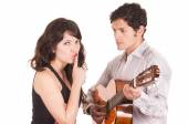 Beautiful girl gesturing silence while young man serenades her with guitar — Stock Photo