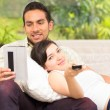 Cute couple lying on the sofa watching tv and using tablet — Stock Photo #64008883