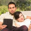 Young attractive couple lying in the sofa using their tablets — Stock Photo #64163111
