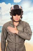 Young handsome pilot wearing uniform and helmet over beach background — Stock Photo