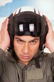 Young handsome pilot wearing helmet over sky background — Stock Photo