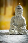 Small sculpture of buddha over white pebbles — Stock Photo