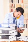 Young stressed overwhelmed man with piles of folders on his desk — Stock Photo