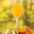 Glass of juice with  kiwi, tree tomato and banana passionfruit slices on a wooden table — Stock Photo #65484929