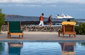 Tourists along the shore enjoying the Galapagos Islands, cruise ship in the background — Stock Photo