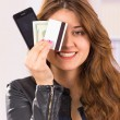 Modern beautiful young woman holding cell phone, money and credit card — Stock Photo #68535043