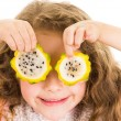 Cute little preschooler girl holding pitahaya slices in front of her eyes — Stock Photo #68708355