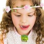 Beautiful healthy little curly girl enjoying eating broccoli — Stock Photo #68710445