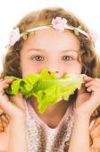 Beautiful healthy little curly girl enjoying eating a lettuce leaf — Stock Photo