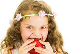 Beautiful healthy little curly girl enjoying eating a red pepper capsicum — Stock Photo
