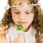 Beautiful healthy little curly girl enjoying eating broccoli — Stock Photo #68873059