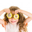 Cute little preschooler girl holding pitahaya slices in front of her eyes — Stock Photo #69070601