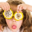 Cute little preschooler girl holding pitahaya slices in front of her eyes — Stock Photo #69072567