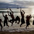 Silhouettes of happy people jumping on the beach at sunset, Galapagos — Stock Photo #69745645