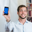 Young happy man holding his cell phone and showing the screen — Stock Photo #70353843