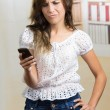 Young beautiful hispanic woman using her cell phone texting — Stock Photo #70687537