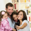Cute family with two little girls taking a selfie photo — Stock Photo #70689381