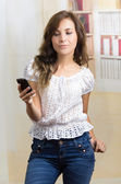 Young beautiful hispanic woman using her cell phone texting — Stock Photo