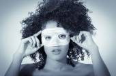 Young woman with short curly dark hair wearing a mask — Stock Photo